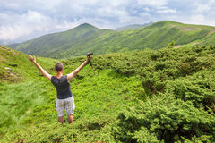 Man standing in mountains with camera raising hands Royalty Free Stock Photography