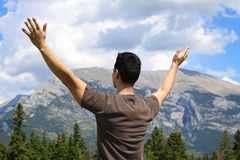Man standing in nature with arms lifted up. Young man standing outdoors in the mountains with arms lifted up royalty free stock image