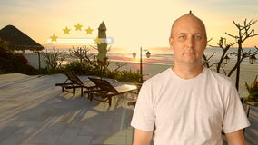 A man standing near the beach at sunset puts a rating of 5 stars for the resort. Virtual screen finger of a man`s hand stock video