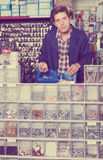 Man standing near the counter and selling details for plumbing i Royalty Free Stock Photos