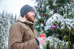 Man standing near decorated christmas tree and drinking coffee outdoors Royalty Free Stock Images