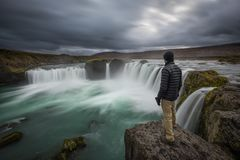 Man standing near the edge of Godafoss waterfall. A hiker standing near the edge of Godafoss waterfall in Iceland stock image
