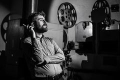 Man standing near a film projector in the room projectionist Royalty Free Stock Photography