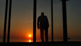Man standing near glass doors of the house at sunset stock video