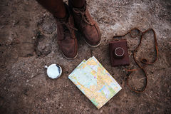 Man standing near map, hip flask and photo camera case Royalty Free Stock Photography