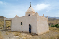 Man standing near a mausoleum in south Morocco stock images