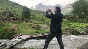 Man standing near mountains river enjoy the view and making picture on smartphone. Travel concept stock video footage