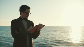 Man is standing near ocean, holding tablet in hands and touching touchscreen. Young guy is browsing internet using big tablet computer in background of sea. He stock footage