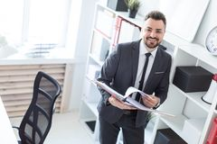 The man is standing near the rack in the office and scrolls through the folder with the documents. A bearded man with a business suit is working in a bright Stock Photos