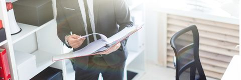The man is standing near the rack in the office and scrolls through the folder with the documents. A bearded man with a business suit is working in a bright royalty free stock photography