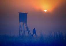 Man standing near raised hide at sunrise Royalty Free Stock Images
