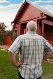 Man standing near red house Stock Image