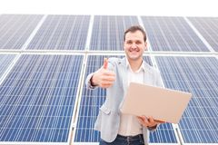Man standing near solar panels, holding laptop, smiling and showing his index finger in front of him. Outdoors. Happy man of European appearance standing against Royalty Free Stock Images