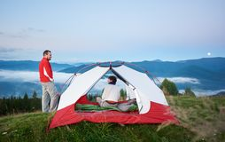 Man standing near the tent in which sits woman against beautiful scenery of mighty mountains. Man standing near the tent in which sits a women against the stock photo