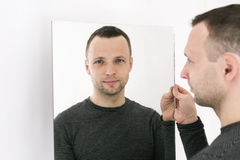 Man standing near white wall with mirror. Studio portrait of young adult European man standing near white wall with mirror royalty free stock photo
