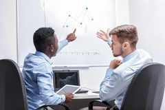 Man standing near whiteboard and pointing on the chart. Two managers sitting at a table and point to the diagram on the whiteboard in the office Stock Photo