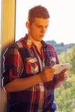 Man standing near window at sunshine using tablet. Smartphone modern technology Stock Photography