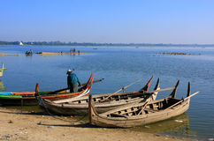 Man standing near wooden boats at the lake, Amarapura, Myanmar Stock Photos