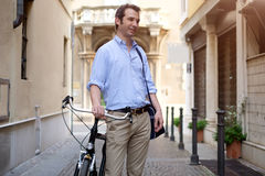 Man is standing next to his bike. In the city streets Stock Images