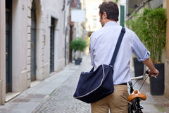 Man is standing next to his bike. In the city streets Stock Photos