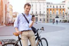 Man standing next to his bike. Hand holding mobile telephone Stock Images