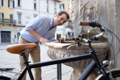 Man is standing next to his bike. Man is resting next to his bike in the city street Stock Photo