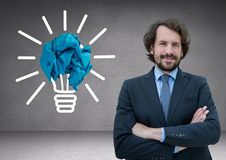 Man standing next to light bulb with crumpled paper ball Royalty Free Stock Image
