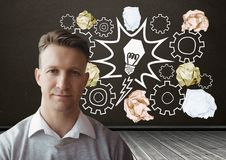 Man standing next to light bulb with crumpled paper balls in front of blackboard. Digital composite of Man standing next to light bulb with crumpled paper balls Royalty Free Stock Images