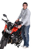 Man standing next to motorcycle Stock Images