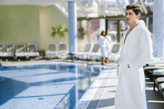 Man standing next to a pool in a  robe Royalty Free Stock Photo