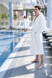 Man standing next to a pool in a  robe Stock Image