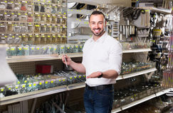 Man standing next to showcase with various plastic rawlplugs an Royalty Free Stock Photography