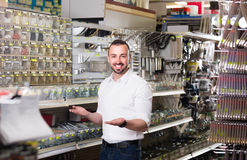 Man standing next to showcase with various plastic rawlplugs an Royalty Free Stock Photo