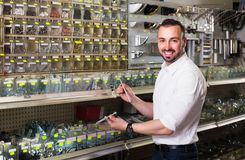Man standing next to showcase with various plastic rawlplugs an Stock Photography