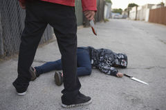 Man Standing Next To Stabbed Woman Lying On Ground. Low section of a male criminal holding blooded knife standing next to stabbed women lying on ground Stock Photos
