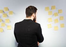Man standing next to a wall with postits. Businessman looking at an wall with many postit notes Stock Image