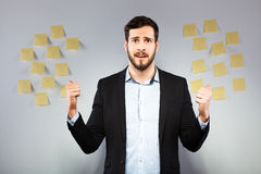 Man standing next to a wall with postits. Young businessman with postit reminder notes on the background Royalty Free Stock Image