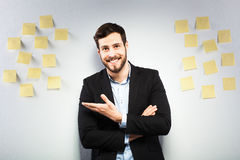 Man standing next to a wall with postits. Young businessman with postit reminder notes on the background Royalty Free Stock Photography