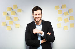 Man standing next to a wall with postits. Young businessman with postit reminder notes on the background Stock Photography