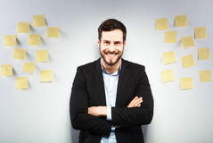 Man standing next to a wall with postits. Young businessman with postit reminder notes on the background Stock Photos