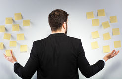 Man standing next to a wall with postits Royalty Free Stock Image