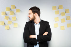 Man standing next to a wall with postits. Young businessman with postit reminder notes on the background Stock Photo