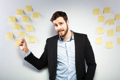 Man standing next to a wall with postits Royalty Free Stock Photography