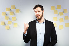 Man standing next to a wall with postits. Young businessman with postit reminder notes on the background Stock Images