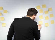 Man standing next to a wall with postits. Young businessman with postit reminder notes on the background Stock Image