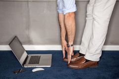 Man standing in office doing exercises with laptop Royalty Free Stock Image