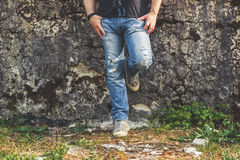 Man standing by the old wall, wearing blue ripped jeans and canvas sneakers. Man standing by the old stone wall, wearing blue ripped jeans and canvas sneakers Royalty Free Stock Photos