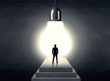Free Man Standing On A Step In Front Of A Huge Light Bulb Royalty Free Stock Image - 76873346