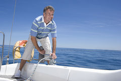 Man Standing On Deck Of Sailing Boat Out To Sea, Winding Rope Pulley Of Boat Rigging, Smiling (tilt) Stock Photography