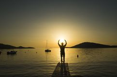 Man standing outdoors on bridge holding hands up in air around sun at beautiful sunset in Croatia royalty free stock photography